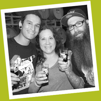 Three people raising a glass of beer.